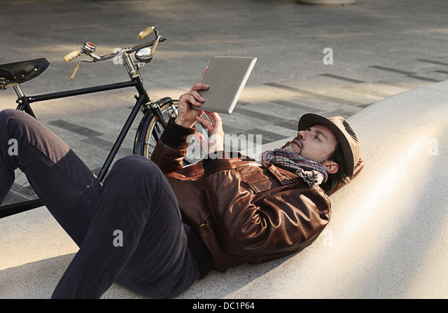 Mid adult man lying on back using digital tablet - Stock Image