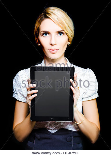 Stylish professional business woman with an inscrutable expression holding up a touchpad tablet with a blank screen - Stock Image