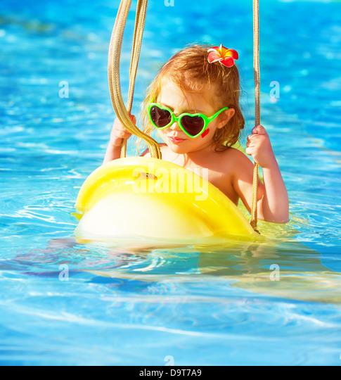 Closeup portrait of cute baby girl swinging on water attractions in aquapark, luxury entertainment on summer resort - Stock-Bilder