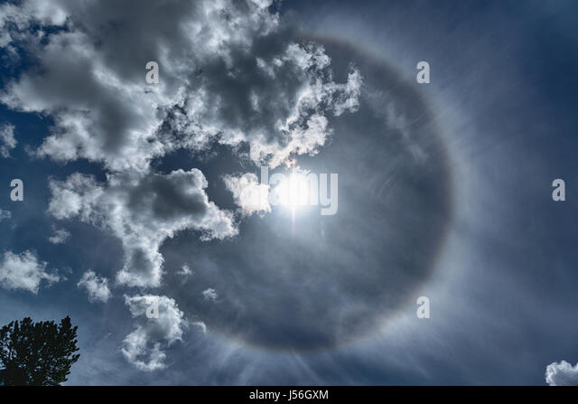 parhelion in the spring sky with clouds and tree seen from the little village of Gressoney Saint Jean in the Aosta - Stock Image