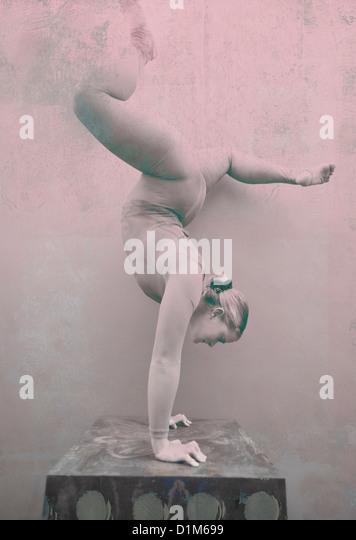 Woman acrobat performing a handstand. Photo based mixed medium image. - Stock Image