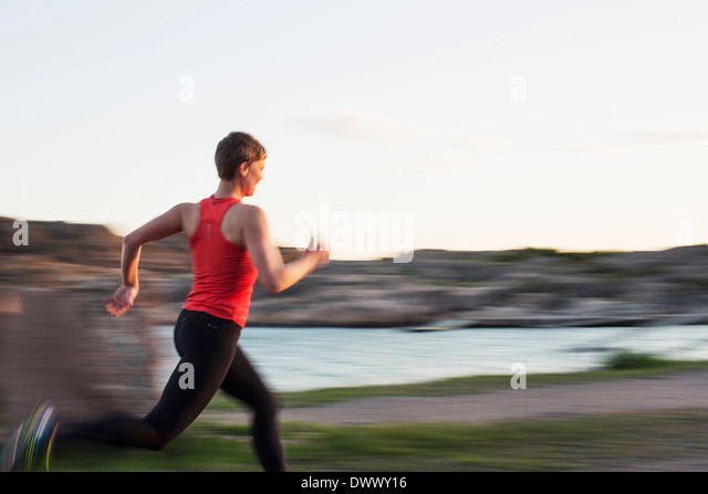 Blurred motion of woman running at lakeshore - Stock Image