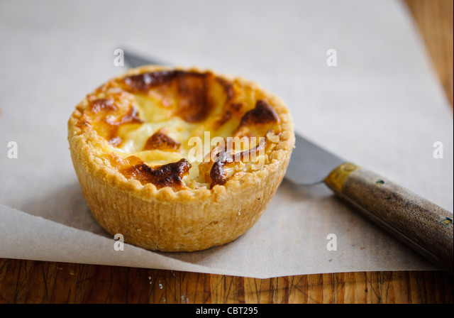 Little Quiche Lorraine on curled greaseproof paper with knife - Stock Image