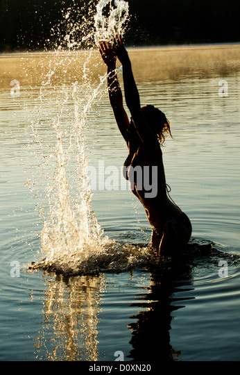 Woman splashing in water of lake - Stock Image