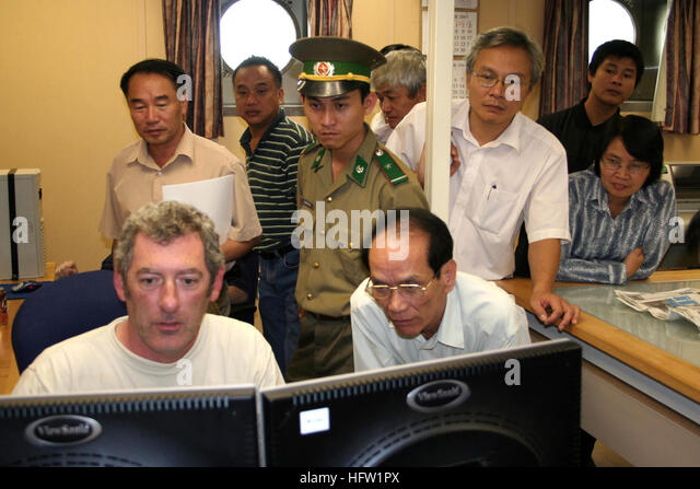071019-N-3392B-002 DA NANG, Vietnam (Oct. 19, 2007) Ð Mr. Neil Duffin, seated left in front of computer monitor, - Stock Image