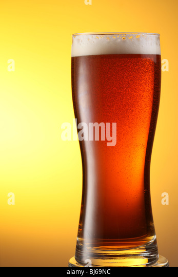 glass of dark beer on a yellow background - Stock Image
