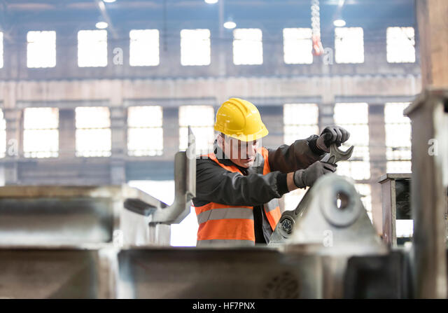 Steel worker using large wrench in factory - Stock Image