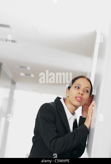 Young businesswoman listening to corridor door - Stock Image