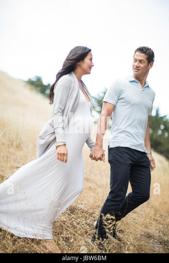 Pregnant woman and mature man, holding hands, walking through field, smiling - Stock-Bilder