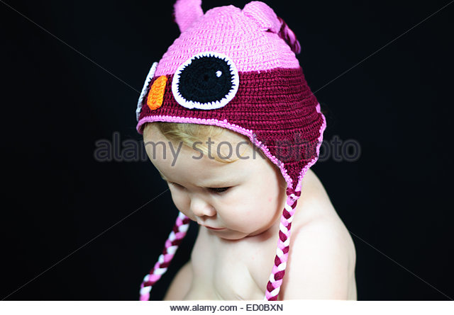 Baby girl (6-11 months) in cap looking down - Stock Image