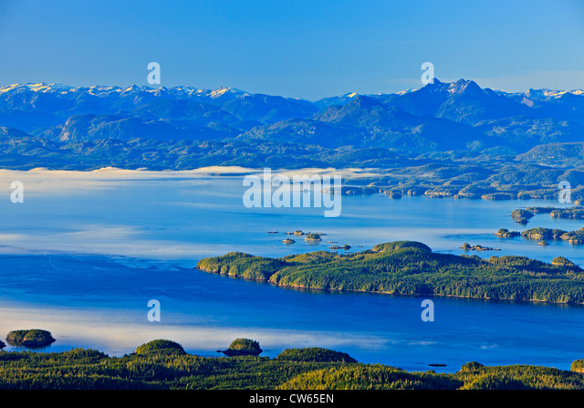 British Columbia Coastal Mountains with Mount Stephens on the right, while fog is rolling in from Queen Charlotte - Stock Image