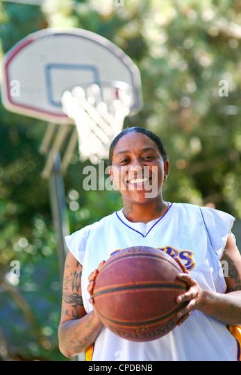 A young African-American woman with tattoos smiles, holding a basketball in front of a basketball hoop. - Stock Image