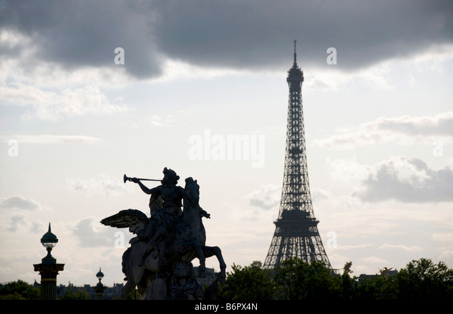 Eiffel tower silhouetted in Paris, France with statue of Renommée, (fame of the king), riding Pegasus in the - Stock Image