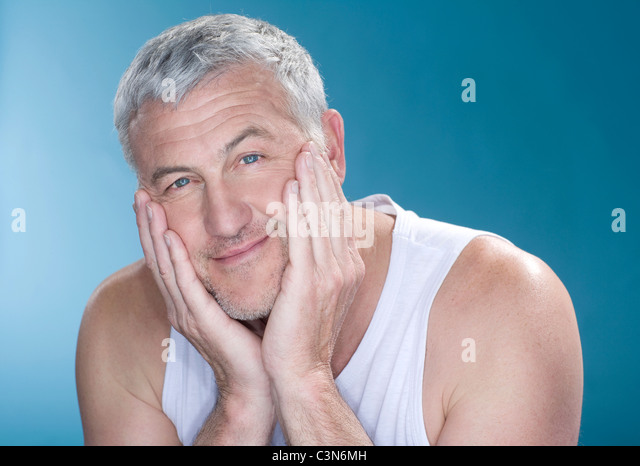 Grey hair man with hands to face happy - Stock Image