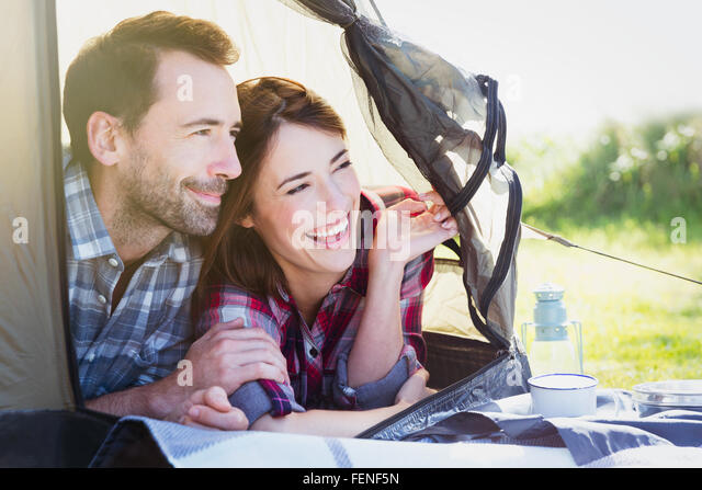 Smiling couple peering from inside tent - Stock Image