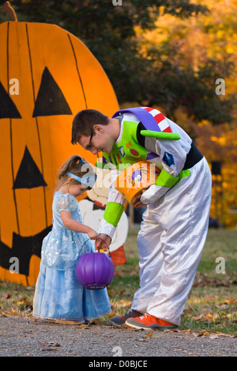 Man in Buzz Lightyear Costume Giving Candy to a Little Girl in A princess Costume during Little Goblens Galore at - Stock Image