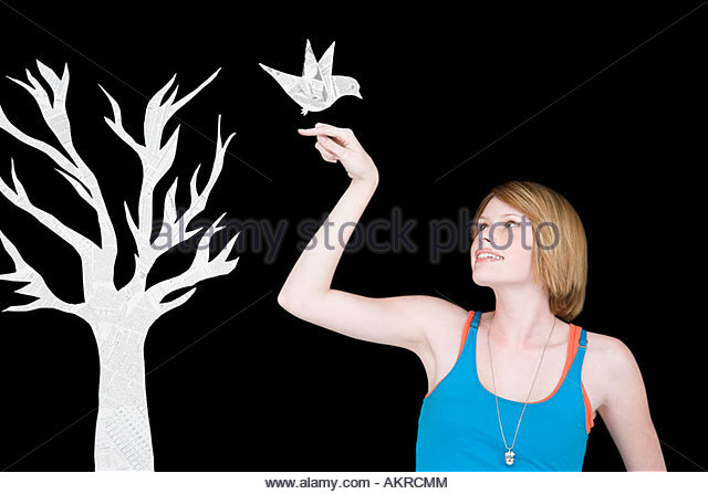 A woman with a fake bird - Stock Image