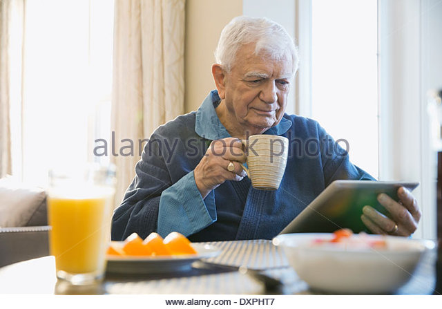 Senior man with digital tablet having coffee at home - Stock Image