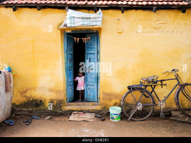 Small indian girl standing in her rustic village house doorway. Andhra Pradesh, India - Stock Image