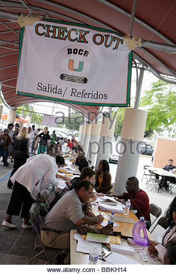 Miami Florida Liberty City Jessie Trice Community Health Center fair free care volunteer exam Black man woman desks - Stock Image