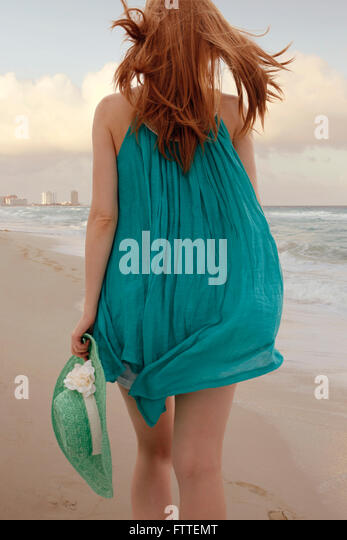 Woman walking on beach - Stock Image