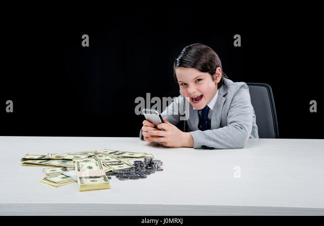 portrait of cunning boy playing businessman and using smartphone on black - Stock Image