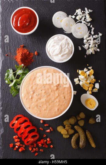 Thousand Island Dressing with ingredients on the table. vertical view from above - Stock Image