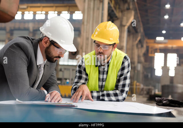 Manager and engineer reviewing blueprints in steel factory - Stock Image
