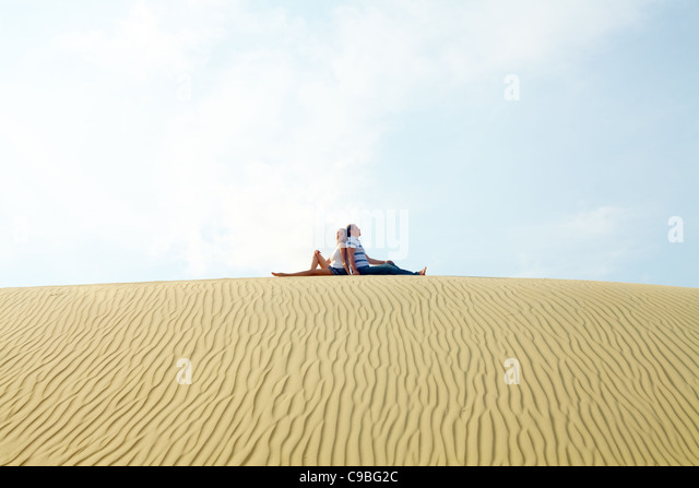Image of restful couple sitting on sandy beach during vacation - Stock Image