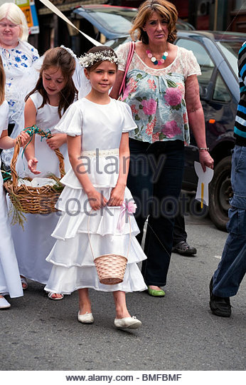 Catholics on parade to mark the festival of Corpus Christi. Catholic procession led by a young girl through Hereford - Stock-Bilder