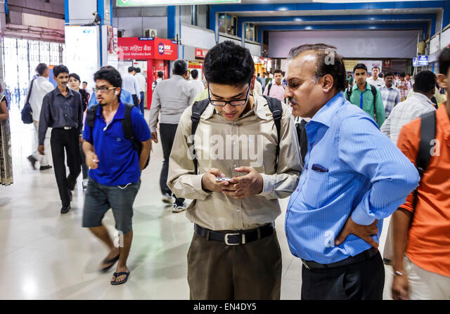 India Asian Mumbai Churchgate Railway Station Western Line train public transportation man looking smartphone - Stock Image
