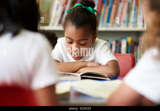 Female Elementary School Pupil Reading In Library - Stock Image