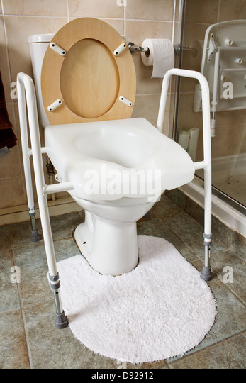 Adjustable height toilet seat fitted to an existing toilet recommended by occupational therapist for elderly, disabled - Stock Image
