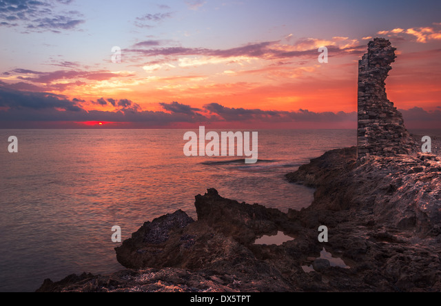 Sunset over the Sea and Rocky Coast with Ancient Ruins and Gate to Africa in Mahdia, Tunisia - Stock Image