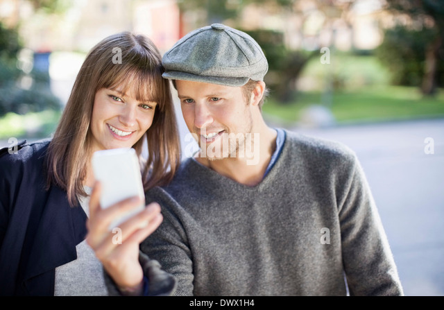 Young couple taking self portrait photography outdoors - Stock Image