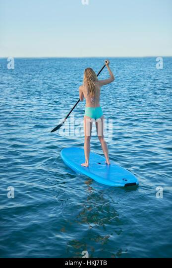Young woman in bikini paddleboarding in summer ocean - Stock-Bilder