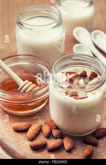 homemade yogurt almond milk with oatmeal and honey on wooden background (Toning) - Stock Image