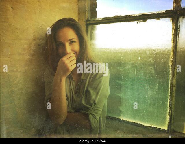 Happy shy woman by the window - Stock-Bilder