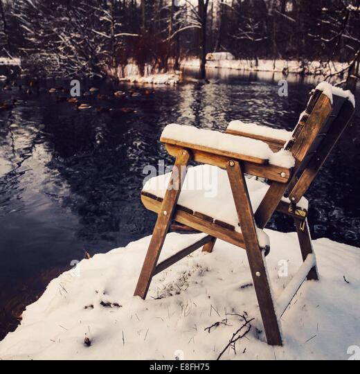 Snow covered chair by lake in winter - Stock Image