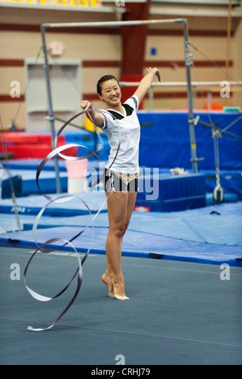 Teenage girl gymnast practicing rhythmic gymnastics, twirling ribbon - Stock Image