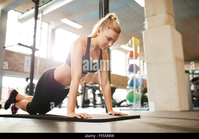 Attractive young female doing push ups on exercise mat. Fitness woman working out in gym. - Stock Image