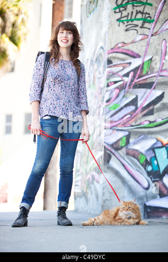 A smiling young woman with a longhaired orange Manx cat on a leash, standing in an urban area with graffiti. - Stock-Bilder