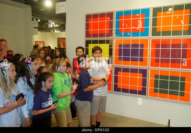 Miami Beach Florida Convention Center centre Art Basel event gallery student classmates class field trip listening - Stock Image