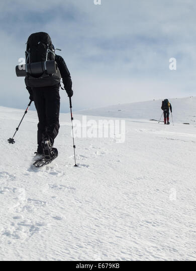 two men with heavy backpacks snowshoeing in winter mountain landscape. Huldraheimen, Gausdal Westfjel, Norway - Stock Image