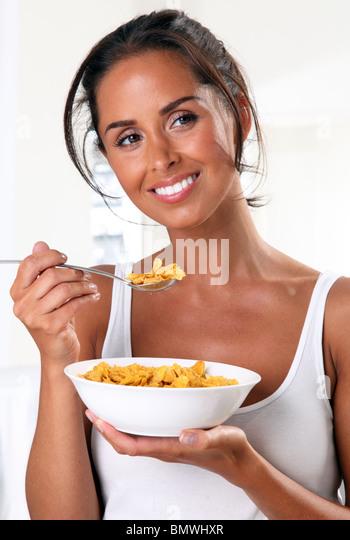 WOMAN EATING CORNFLAKES - Stock Image