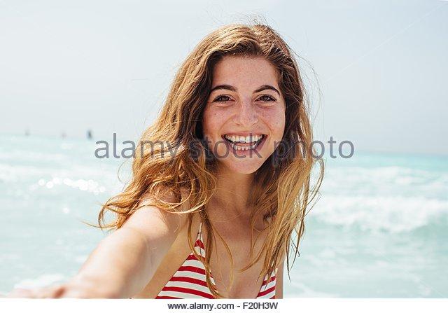 Portrait of young woman wearing bikini in sea - Stock Image