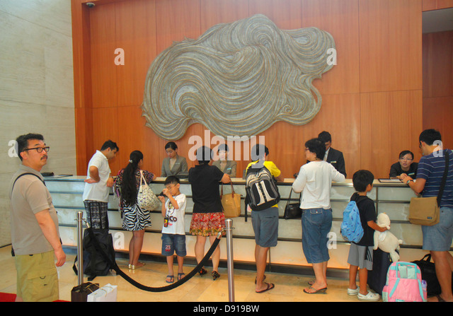 Singapore Marina Bay Sands hotel lobby front desk check-in Asian man woman family - Stock Image