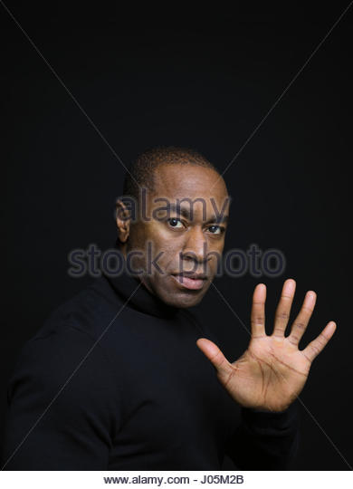 Portrait serious African American man gesturing with hand against black background - Stock Image