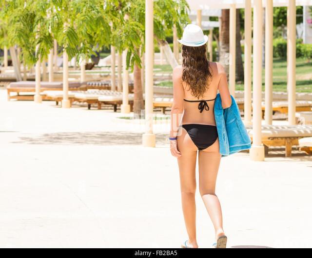 Slim woman in black bikini walking at the poolside along sun loungers. Summer resort background - Stock-Bilder