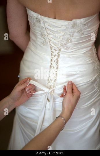 bridesmaid tying the bow on a wedding dress of a bride on her wedding day - Stock Image